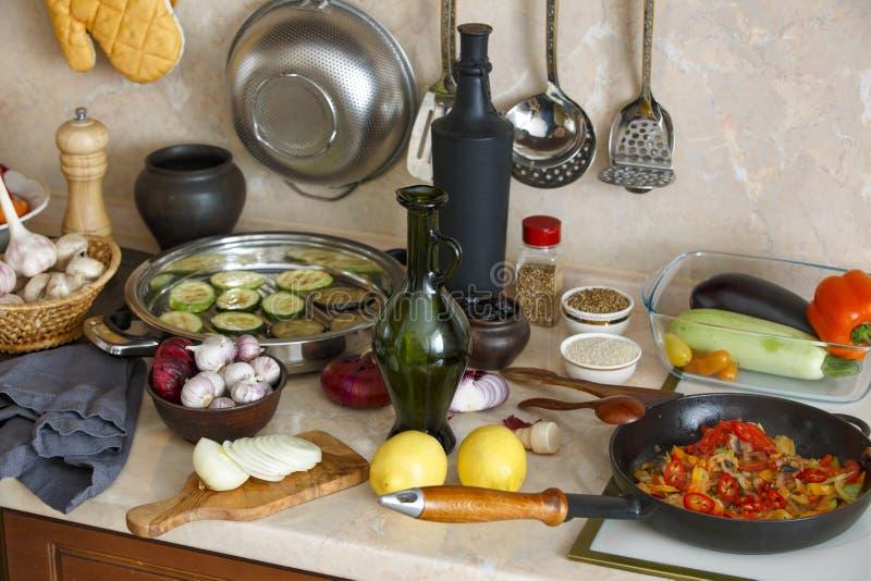 Ustensiles, bouteilles, légumes et condiments de cuisine sur le kitc photo stock