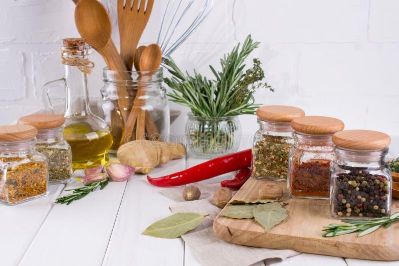 Ustensiles de cuisine, herbes, épices sèches colorées dans des pots en verre photo stock