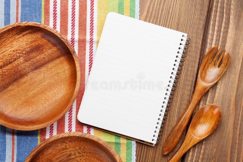 Ustensiles en bois de cuisine avec le bloc-notes pour l'espace de copie images stock