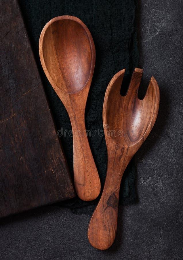 Ustensiles en bois de cuisine de vintage au-dessus de tissu noir sur le fond en pierre de table Vue supérieure photographie stock libre de droits