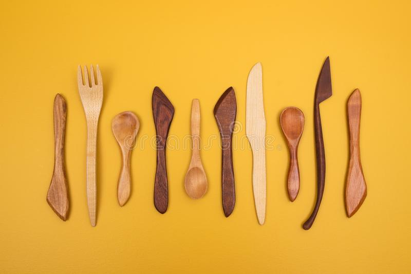 Ustensiles en bois Handcrafted sur le fond jaune images stock