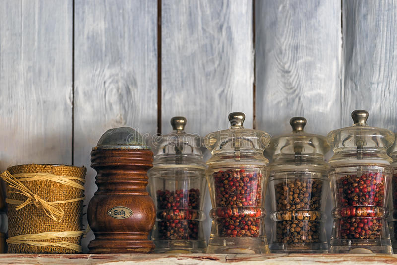 Ustensiles, herbes et épices de cuisine sur l'étagère contre le mur en bois rustique photos stock
