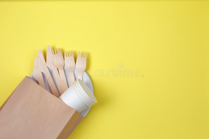 Ustensiles jetables qui respecte l'environnement faits de bois et papier en bambou sur le fond jaune images stock