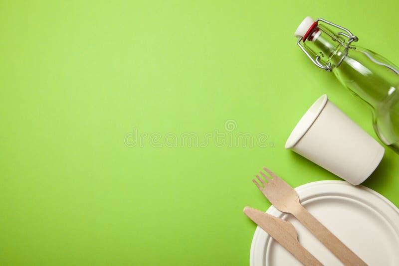 Ustensiles jetables qui respecte l'environnement faits de bois et papier en bambou sur un vert Cuillères drapées, fourchette, cou photos stock