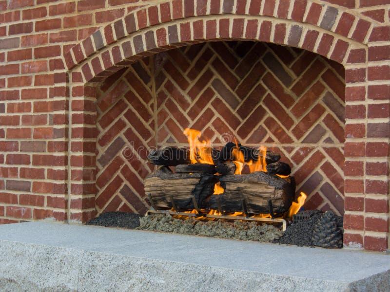 Ustioni allegre del fuoco nello spazio all'aperto del riscaldamento del camino del mattone immagini stock