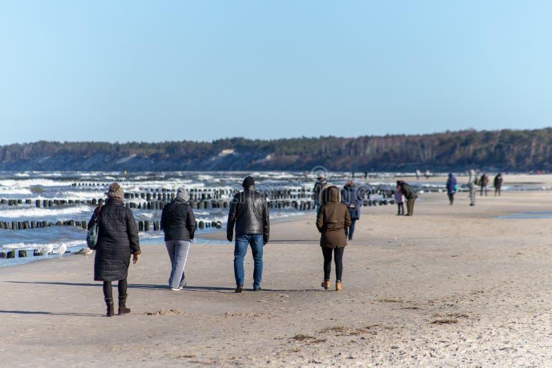 Ustka, Pomorskie/Польша - 22-ое февраля 2019: Люди идя вдоль пляжа на seashore Прогулка зимы в солнечной погоде стоковое фото