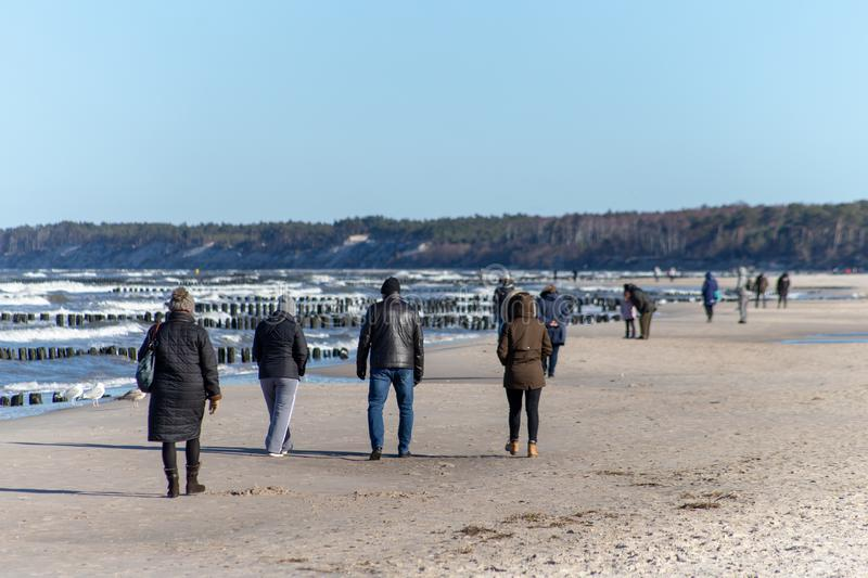 Ustka, Pomorskie / Poland - February, 22, 2019: People walking along the beach on the seashore. A winter walk in sunny weather stock photo