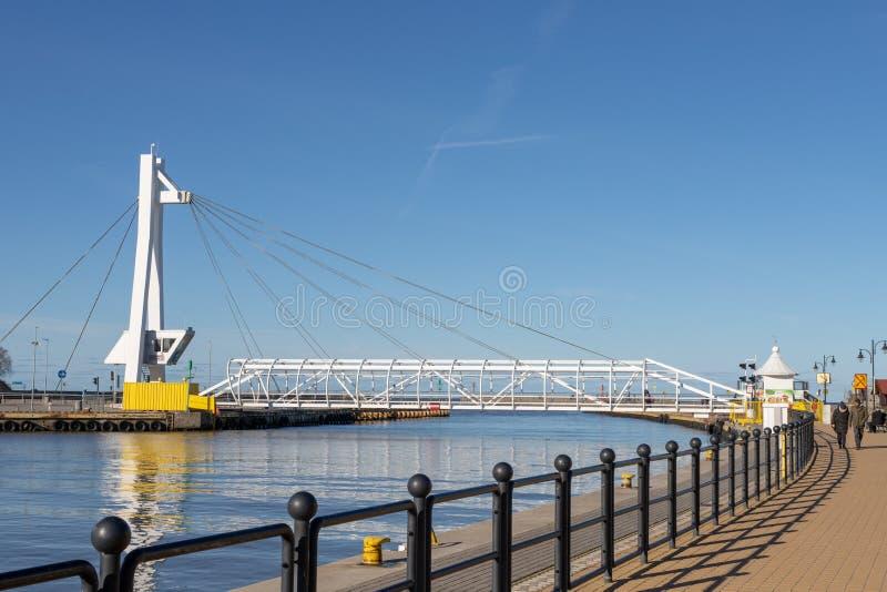 Ustka, pomorskie/Pologne - février, 22, 2019 : Pont piétonnier par le canal gauche dans Ustka Bâtiments de port en Pologne photo stock