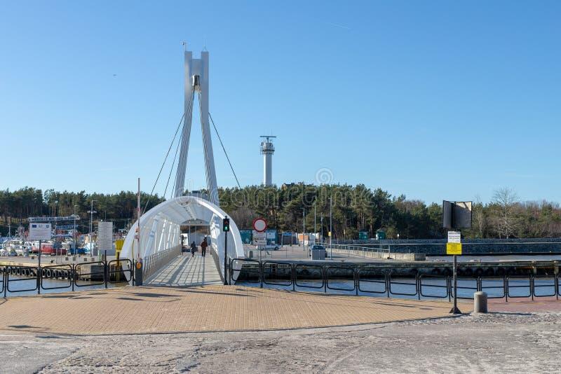 Ustka, pomorskie/Pologne - février, 22, 2019 : Pont piétonnier par le canal gauche dans Ustka Bâtiments de port en Pologne photographie stock libre de droits