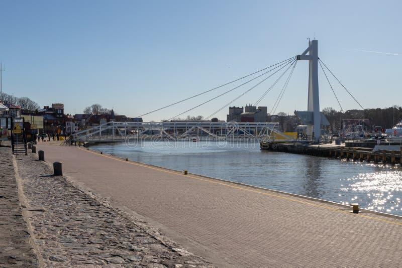 Ustka, pomorskie/Pologne - février, 22, 2019 : Pont piétonnier par le canal gauche dans Ustka Bâtiments de port en Pologne photo libre de droits