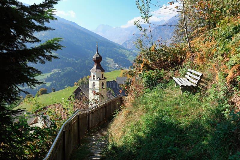 Ustronna drewniana ławka na zbocze góry przegapia wysokogórską wioskę Stulles Południowy Tyrol, Włochy zdjęcia stock