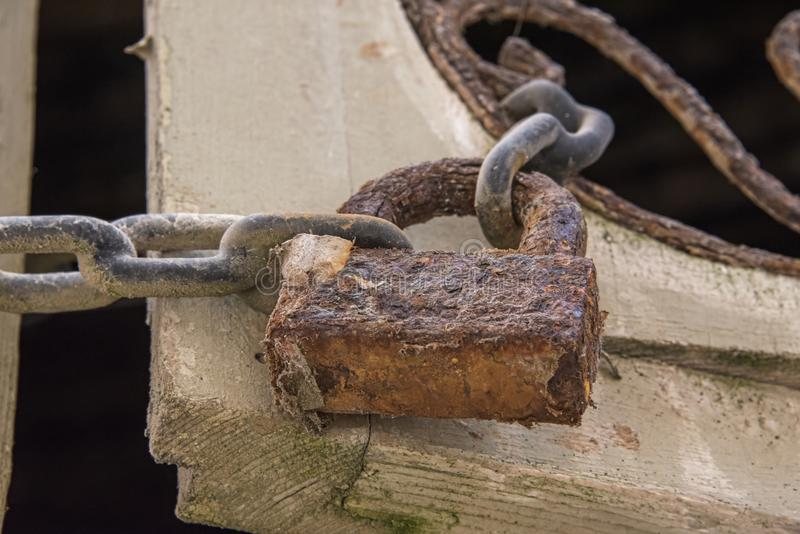 Usty挂锁&链子 相连有生锈的金银细丝工的细节的快门 免版税库存照片