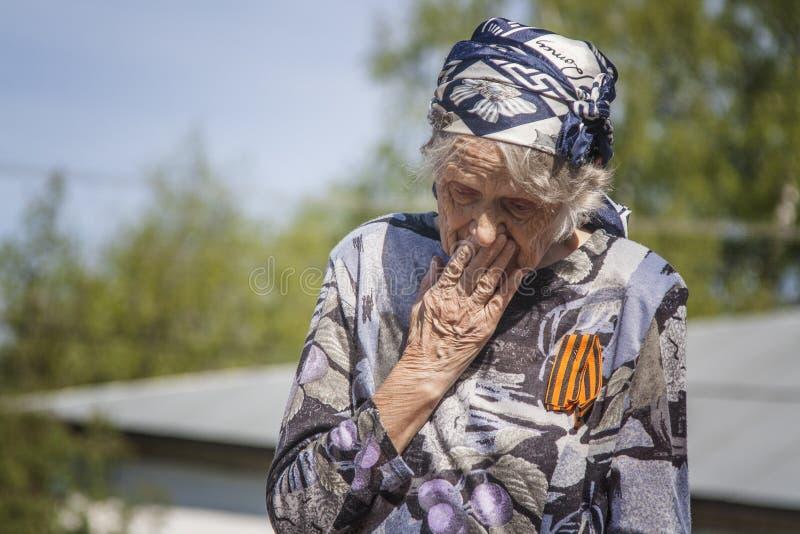Ustyuzhna Vologda region, Ryssland-Maj 9, 2016 Beröm av segern i världskrig II En veteran för gammal kvinna i en sjalett och e royaltyfri foto