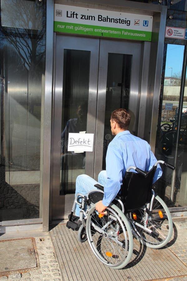 Usuário de cadeira de rodas em um elevador do defeito imagens de stock royalty free