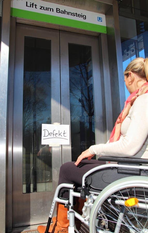 Usuário de cadeira de rodas fêmea em um elevador do defeito foto de stock