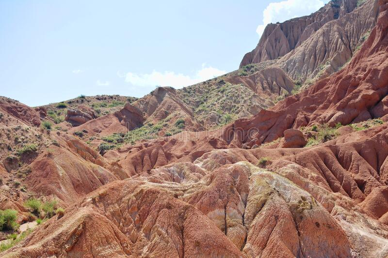 Unusual beautiful nature of the canyon in Kyrgyzstan. Red mountains against the blue sky. royalty free stock image