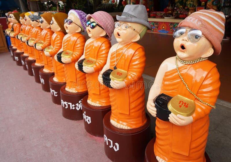 Usura della statua del monaco del bambino occhiali Sta tenendo la ciotola delle elemosine fotografia stock libera da diritti