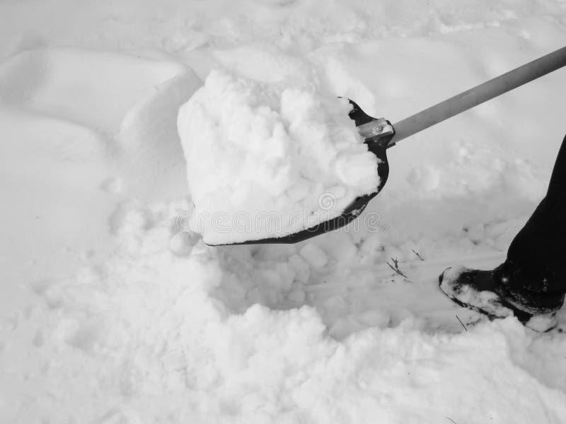 Usuwać śnieg z łopatą po opadu śniegu fotografia stock