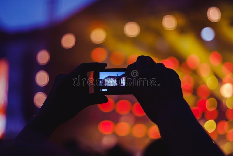 Usuwający na telefonie przy koncertem obraz stock
