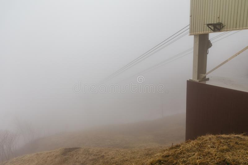 Usuzan Ropeway pole that cable disappear in the fog, view from Mount Usu in Hokkaido, Japan.  royalty free stock photography