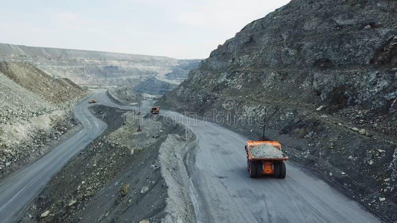 Usyp ciężarówka jest przy łupem Odgórny widok napędowa pomarańczowa usyp ciężarówka z gruzem na drogowej otwartej jamie Ciężki tr obraz royalty free