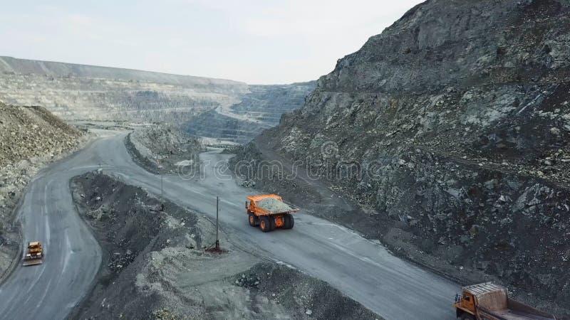 Usyp ciężarówka jest przy łupem Odgórny widok napędowa pomarańczowa usyp ciężarówka z gruzem na drogowej otwartej jamie Ciężki tr zdjęcie royalty free