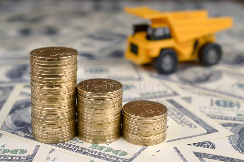 Usyp ciężarówki zabawka i sterty złociste monety na tle wiele sto dolarowych rachunków zdjęcia stock