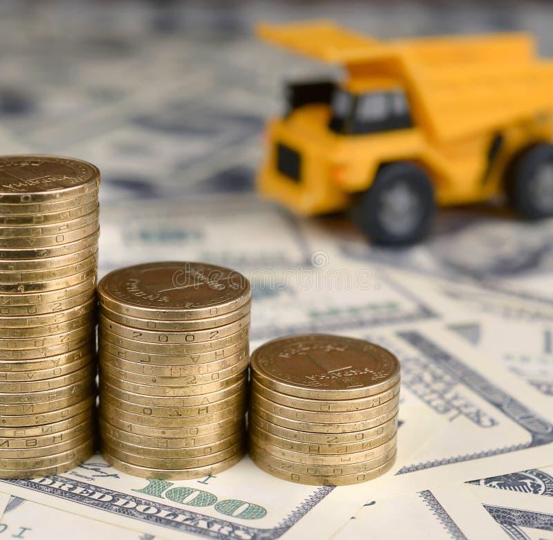 Usyp ciężarówki zabawka i sterty złociste monety na tle wiele sto dolarowych rachunków zdjęcie royalty free