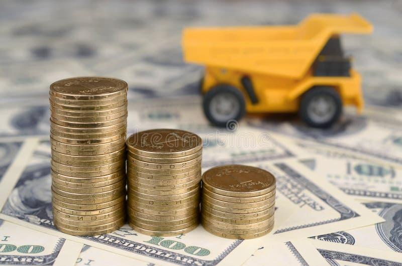 Usyp ciężarówki zabawka i sterty złociste monety na tle wiele sto dolarowych rachunków obrazy royalty free