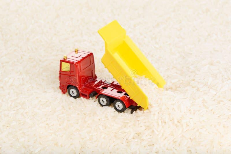 Usyp ciężarówki zabawka rozładowywa ryżowe adra obraz stock