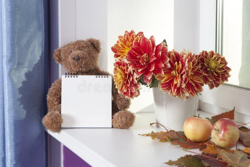 Uszatek obok bukieta jesieni dalie Uszatek trzyma notepad dla pisać obrazy royalty free