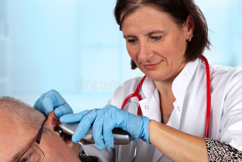 Uszaty egzamin lekarką z otoskopem zdjęcie royalty free