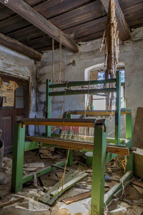 Uszkadzająca rocznika tkactwa maszyna w starym zaniechanym domu z grunge ściennym i drewnianym sufitem fotografia royalty free