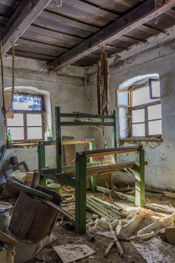 Uszkadzająca rocznika tkactwa maszyna w starym zaniechanym domu z grunge ściennym i drewnianym sufitem zdjęcia royalty free