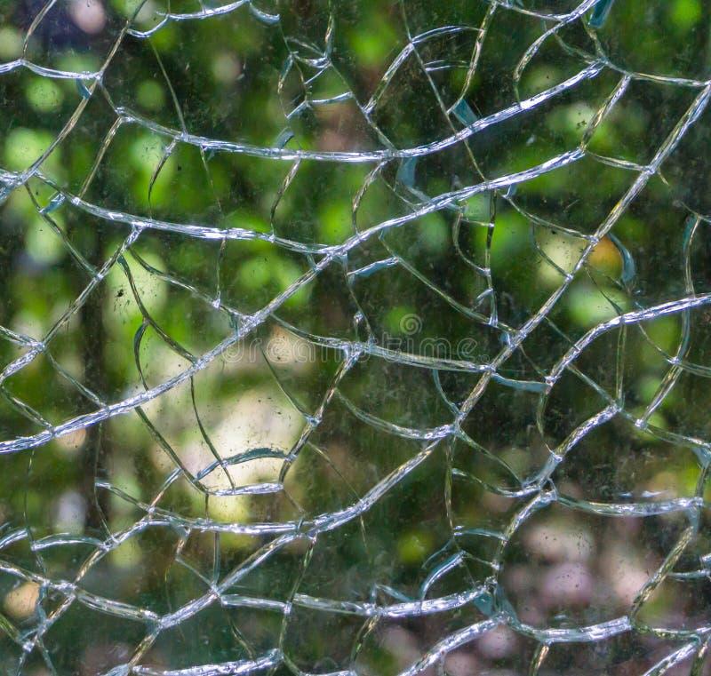 Uszkadzający łamający i rozbijający w kawałka szklanego okno w makro- zakończeniu w górę zadziwiającej tło tekstury obraz royalty free