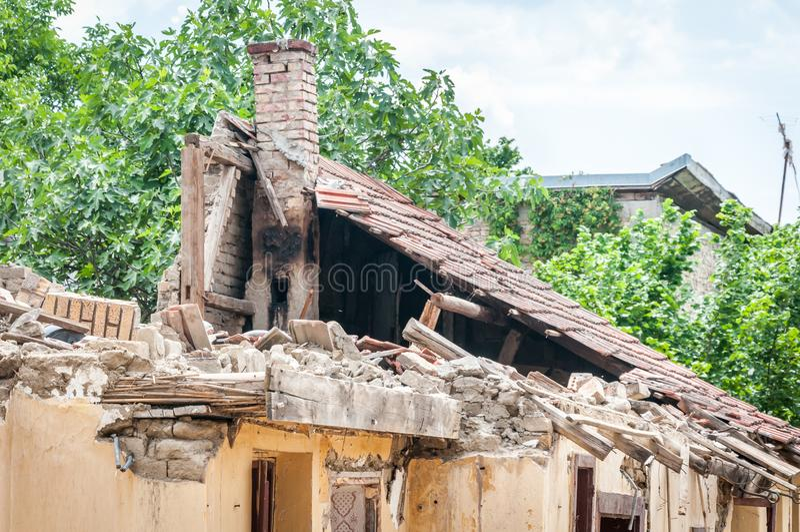 Uszkadzający i łamający zawalony dach zaniechany dom po tym jak ogień od granat bomby z płytkami i markotnym nieba tłem zdjęcie royalty free