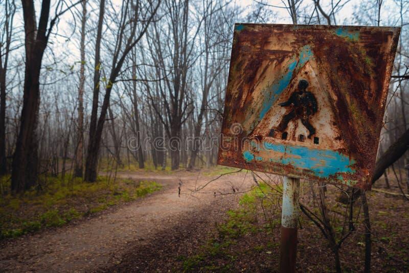 Uszkadzający pieszy znak przy forestal drogą zdjęcia royalty free