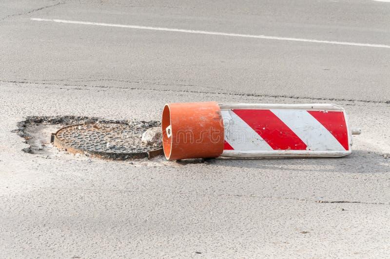 Uszkadzający uliczny ostrożności bielu i czerwieni znak odbudowy lub budowy zakrywa otwartej dziury manhole na drodze jako a obraz royalty free