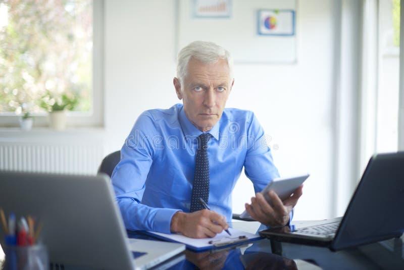 Utövande affärsman som arbetar i kontoret royaltyfri foto