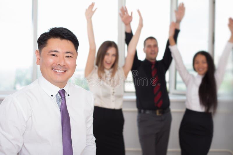 Utövande asiatiskt framstickande med hans lyckade affärslag på bakgrund royaltyfri bild