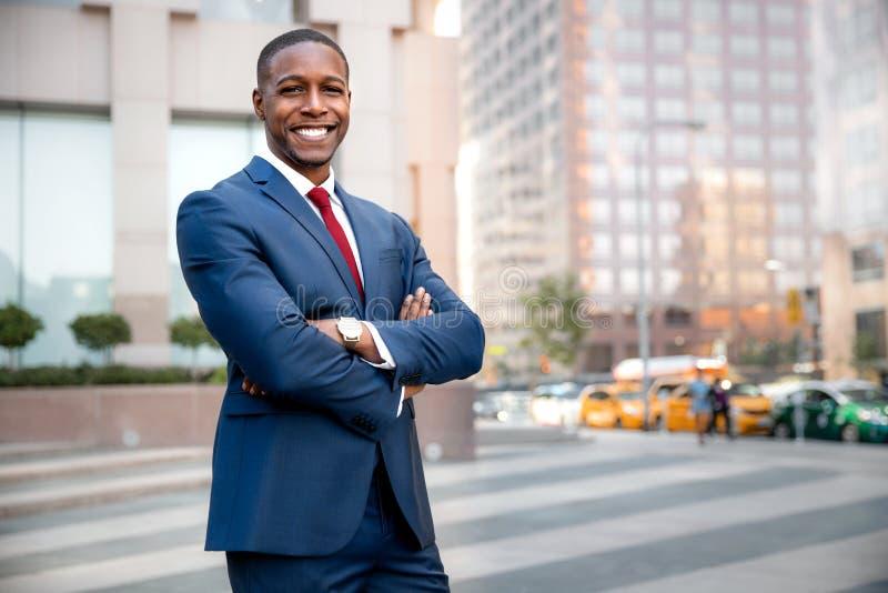 Utövande vdafrikansk amerikan för stolt lyckad affärsman som säkert står med armar vikta i i stadens centrum finansiell byggnad royaltyfri bild