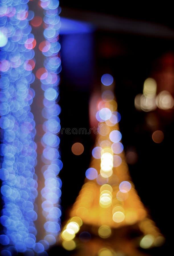 Ut ur fokus suddigt, Bokeh, Defocused blått och gult ljus i en trädgård på natten, för abstrakt bakgrund arkivfoton