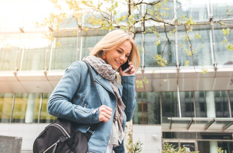 Ut?vande arbete med en mobiltelefon i gatan med kontorsbyggnader i bakgrunden royaltyfria bilder