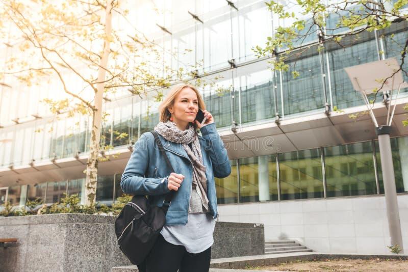 Ut?vande arbete med en mobiltelefon i gatan med kontorsbyggnader i bakgrunden arkivfoton