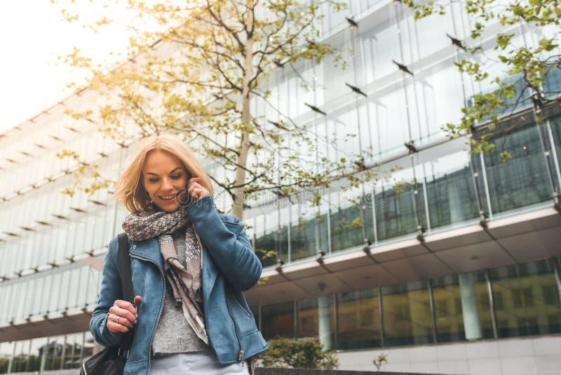 Ut?vande arbete med en mobiltelefon i gatan med kontorsbyggnader i bakgrunden arkivfoto