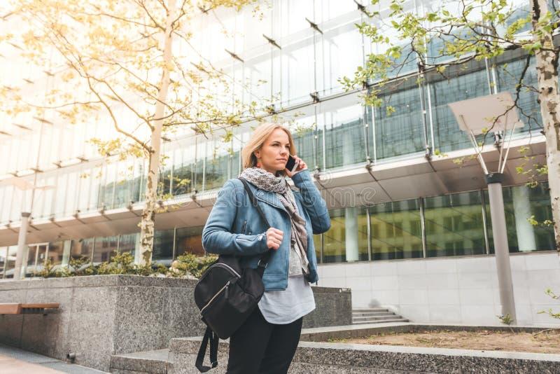Ut?vande arbete med en mobiltelefon i gatan med kontorsbyggnader i bakgrunden royaltyfri bild