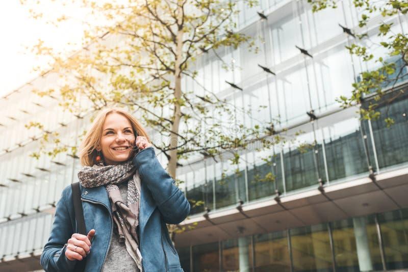 Ut?vande arbete med en mobiltelefon i gatan med kontorsbyggnader i bakgrunden royaltyfria foton