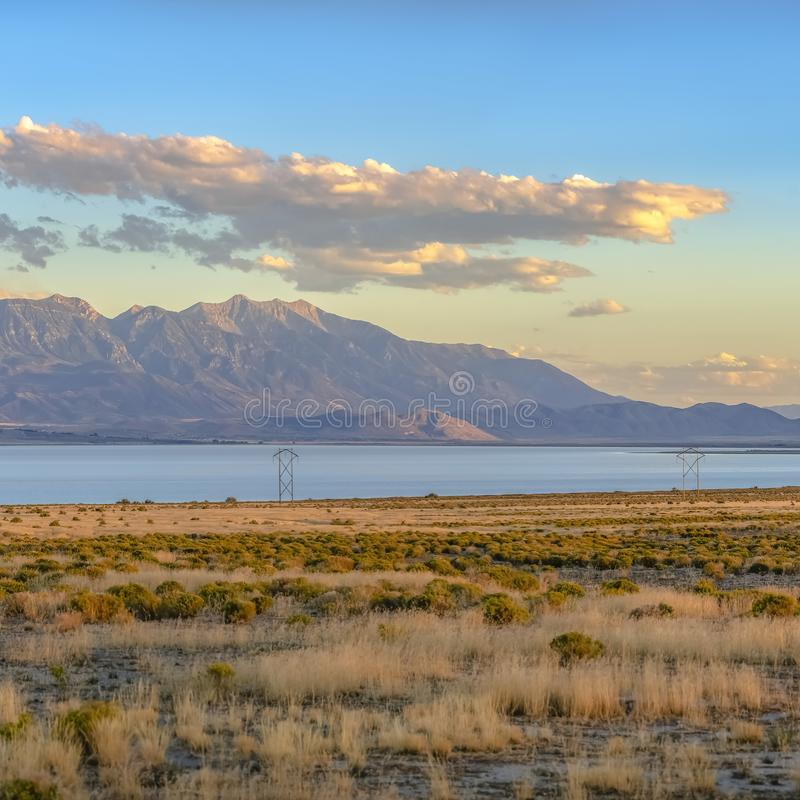 Utah Lake and mountain beyond a grassy terrain. The calm Utah lake seen beyond a grassy terrain at sunset. Striking mountain and blue sky with puffy clouds can royalty free stock photos