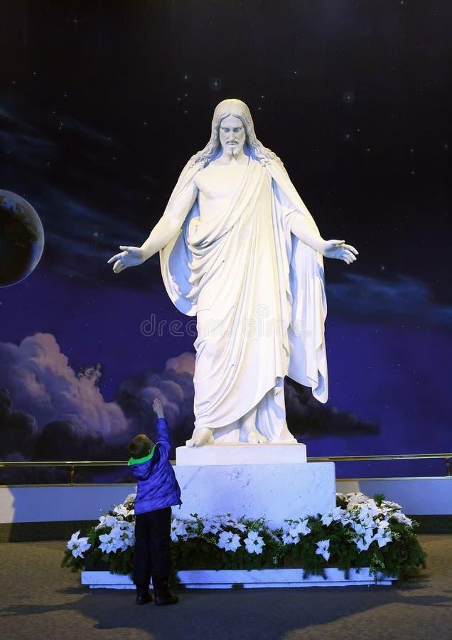 Utah, los E.E.U.U. - 21 de diciembre de 2016: una estatua de mármol de Jesus Christ con brazos abiertos y un muchacho que estira foto de archivo