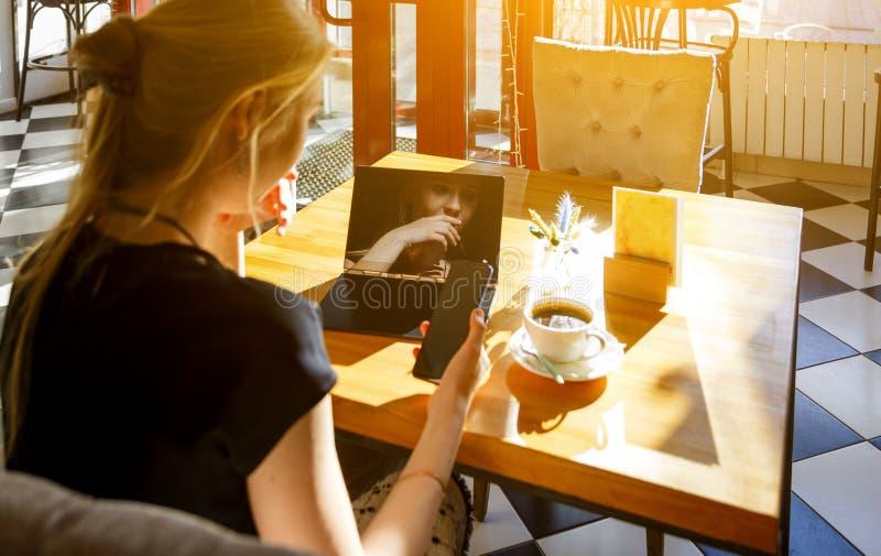 Utalentowany żeński uczeń w kawiarni używać nowożytnych gadżety zdjęcia stock
